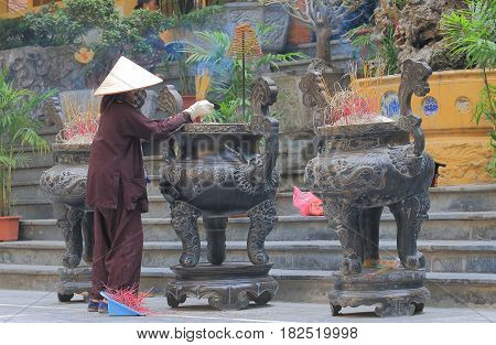 HANOI VIETNAM - NOVEMBER 22, 2016: Unidentified woman cleans at Quan Su Temple. Quan Su Temple was built in the 15th century under the Le Dynasty.