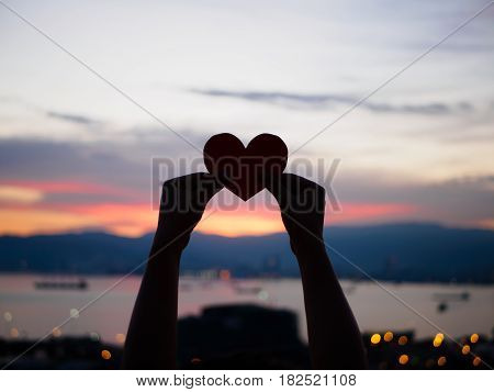 silhouette hand is raising the red paper heart with blur sunlight during sunset Valentines day