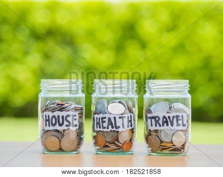 A lot coins in glass money jar on the wood table. Saving for house health and travel concept.