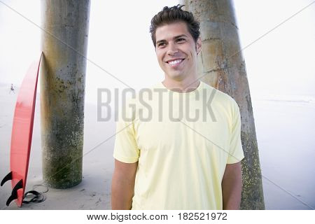 Hispanic man in front of surfboard
