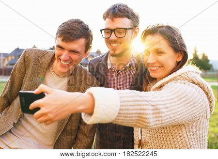 Friendship leisure spring technology and people concept - smiling friends making selfie outdoors
