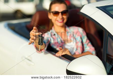 Young pretty woman sitting in a convertible car with the keys in hand - concept of buying a used car or a rental car