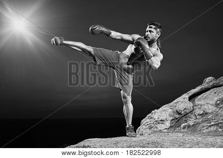 Horizontal full length portrait of a shirtless muscular fighter exercising outdoors kickboxing combat sport sportsman athlete muscular strong effort competitive practicing workout concept monochrome