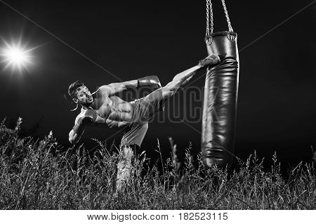 Black and white shot of a professional kick boxer practicing on a heavy punching bag outdoors at night copyspace motivation lifestyle workout muscles power strength masculinity martial sportsperson.