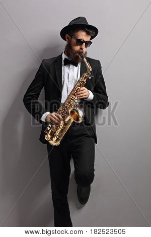 Jazzer playing on a saxophone and leaning against a gray wall