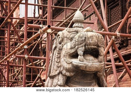 Scaffolding set up to support one of the many structures damaged in the 2015 earthquake surrounds an ornately carved statue. Durbar Square Kathmandu.