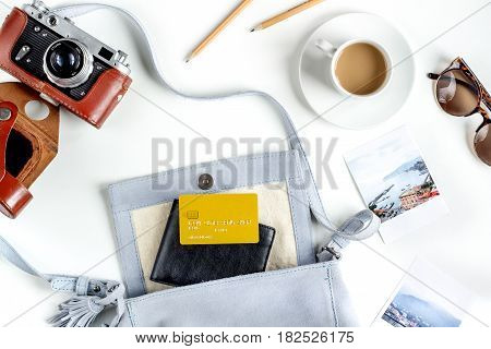 vacation concept with traveller outfit bag, camera, coffee on white desk background top view
