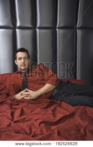 Man wearing shirt and tie on bed