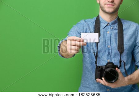 Handsome photographer with business card on color background