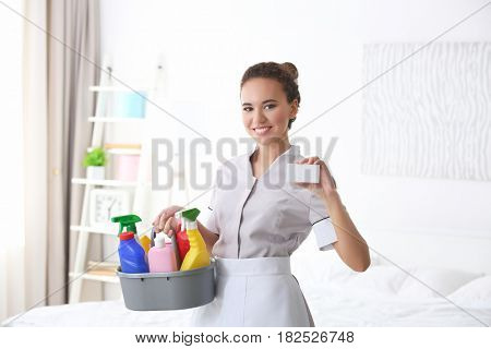 Young African American chambermaid with business card and cleaning supplies indoors