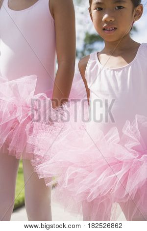 Asian sisters in ballet outfits outdoors