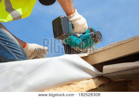 Installing a skylight. Construction Builder Worker use Circular Saw to Cut a Roof Opening for window