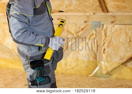 Construction mason worker with building level and screwdriver on attic with environmentally friendly and energy efficient thermal insulation rockwool.