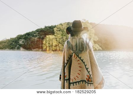 Boho style woman wearing in poncho and hat walking on lake rear view.