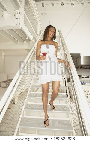 African American woman on stairs with cocktail