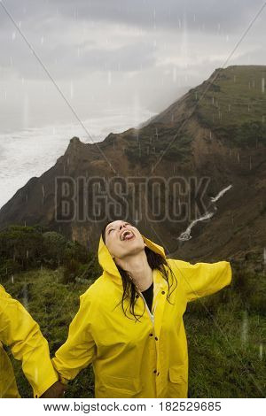 Hispanic woman in rain gear with face turned up