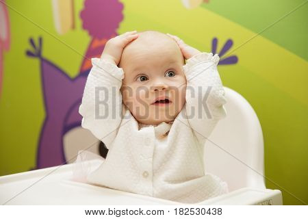 baby without hair grabbed his head with surprise
