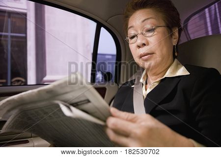 Asian businesswoman reading newspaper in car