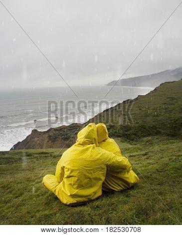 Hispanic couple in rain gear sitting in grass