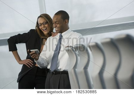 African business people looking at cell phone and smiling