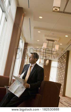 Businessman holding newspaper in lobby