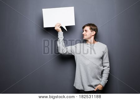 Young Man Holding White Blank Speech Bubble With Space For Text Look Away Isolated On Grey Backgroun