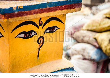 Buddha eyes also known as wisdom eyes on a stupa in Nepal. Background of construction materials (sandbags) one of the many construction sites present in Nepal after the 2015 earthquake.