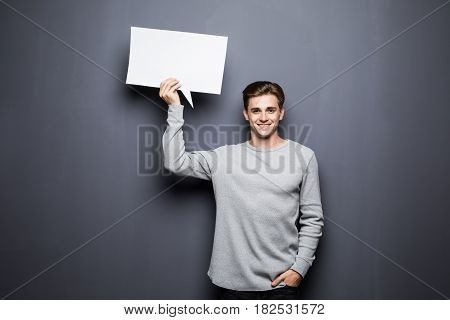 Young Smile Man Holding White Blank Speech Bubble With Space For Text Isolated On Grey Background.