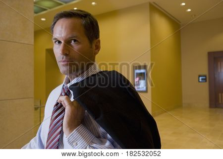 Businessman holding suit jacket over shoulder