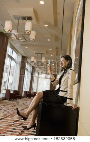 Mixed race businesswoman looking at cell phone in corridor