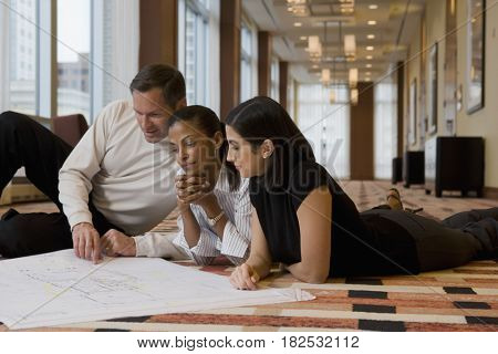 Multi-ethnic business people laying on floor reviewing blueprints