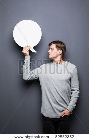 Young Man Holding White Blank Speech Bubble With Space For Text Isolated On Grey Background.