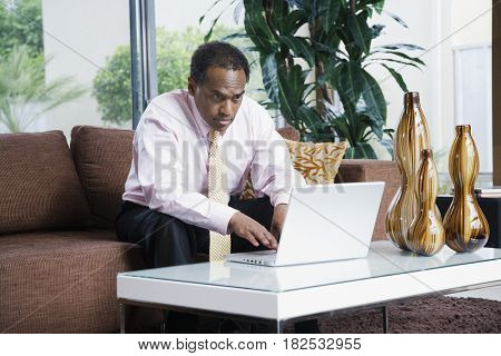 Serious African businessman typing on laptop in living room