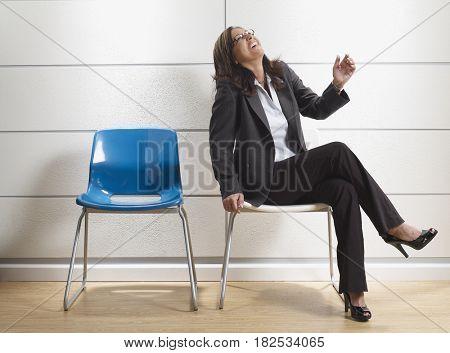 Hispanic businesswoman laughing in waiting room