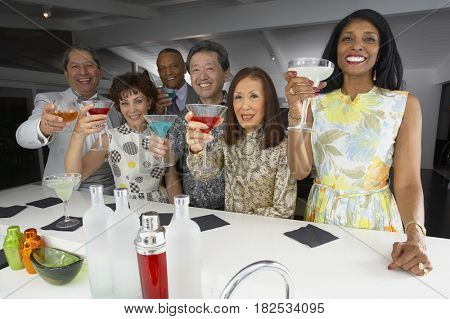 Multi-ethnic group of friends drinking cocktails at party