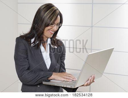Hispanic businesswoman holding laptop