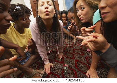 Multi-ethnic group of friends playing spin the bottle