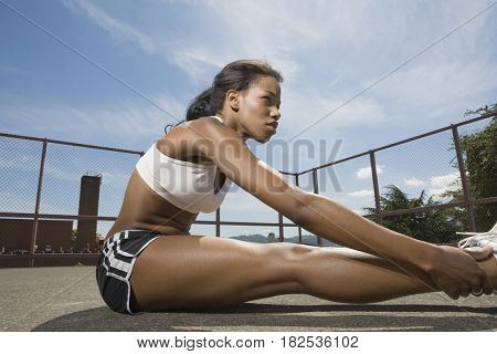 African American woman stretching on pavement