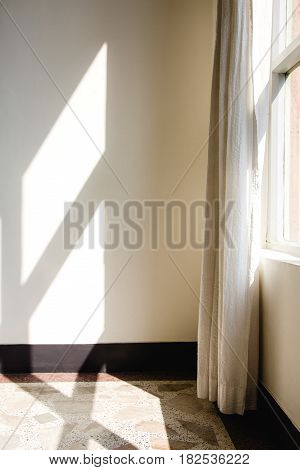 Early morning light streaming through a window and onto a floor made of terrazzo tiles and wall.