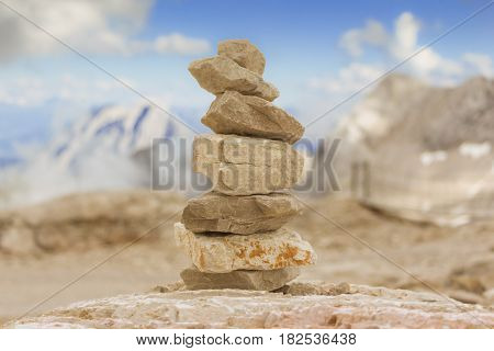 Big stone tower in mountains height show balance stability power. Stones stack in mountain panorama with blue sky visualizes creativity consulting success or showing health meditation and therapy.
