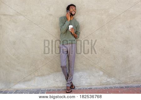 African Man Leaning Against Wall With Cellphone And Coffee