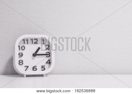 Closeup white clock for decorate show a quarter past one o'clock or 1:15 p.m. on white wood desk and cream wallpaper textured background in black and white tone with copy space