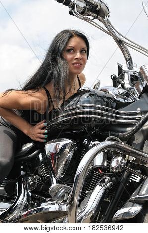 attractive biker woman sitting on her motorcycle at the motorbike show