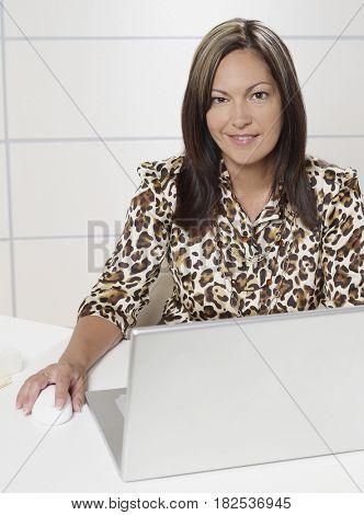 Hispanic businesswoman working at laptop
