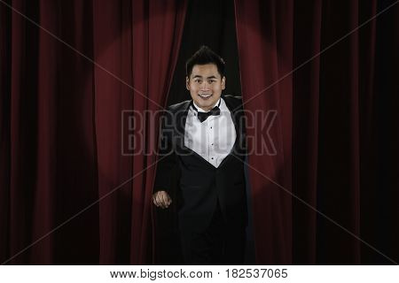 Asian man in tuxedo emerging from behind red curtain
