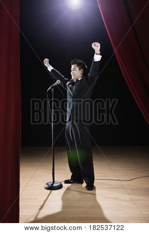 Asian man in tuxedo standing at microphone with arms raised