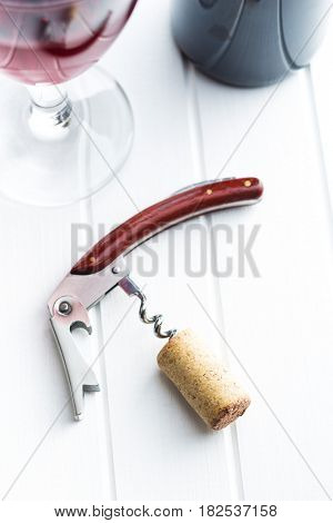 Cork and corkscrew on white table.