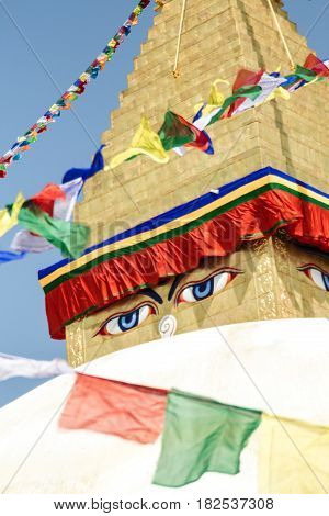Closeup of the Buddha eyes of Boudhanath stupa surrounded by prayer flags in Kathmandu Nepal. It is the largest stupa in Nepal and the holiest Tibetan Buddhist temple outside Tibet.