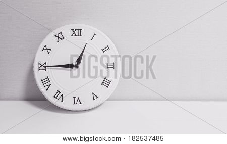 Closeup white clock for decorate show a quarter to one o'clock or 12:45 p.m. on white wood desk and wallpaper textured background in black and white tone with copy space