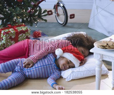 African American brother and sister sleeping by Christmas tree